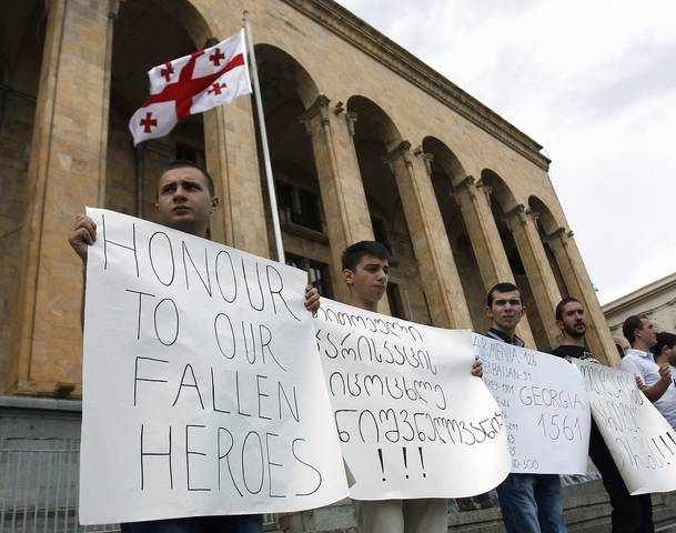 People hold a rally to demand the withdrawal of Georgian troops from Afghanistan, in Tbilisi