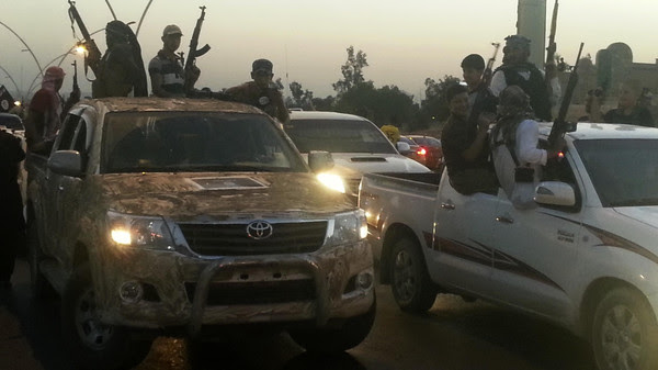 Fighters of the ISIL celebrate while sitting on vehicles in Mosul