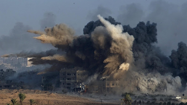 An explosion during an Israeli strike in the northern Gaza Strip is pictured from the Israeli border with Gaza, before a cease-fire takes effect