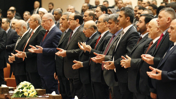 Members of the new Iraqi parliament recite verses from the Koran at the parliament headquarters in Baghdad