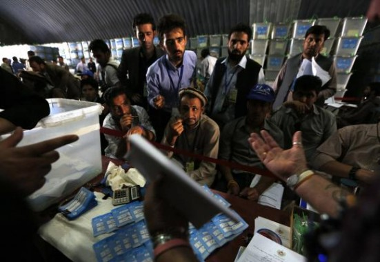 Afghan election workers count ballot papers during an audit of the presidential run-off in Kabul
