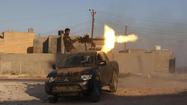 A fighter from armed group Operation Dawn fires a weapon during clashes with rival group the Zintan brigade, on the outskirts of Kklh