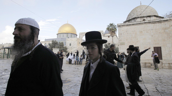 Ultra-Orthodox Jews walk in front of the Dome of the Rock in Jerusalem's Old City