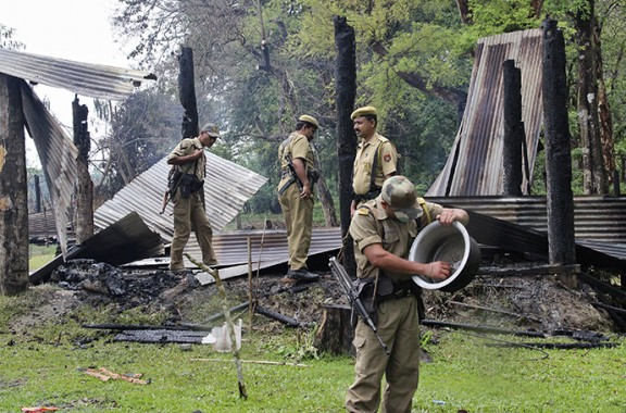 Indian security personnel inspect the debris of the houses that were burnt during attacks at Baksa district