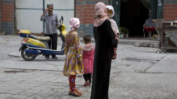"""In this photo taken Thursday, July 17, 2014,  a Uighur woman wears a full length garment and headscarf associated with conservative Islam in the city of Aksu in western China's Xinjiang province.  In China's restive western province of Xinjiang, young men of the Uighur ethnic minority are not allowed to have beards. Also proscribed are certain types of women's headscarves, veils and """"jilbabs,"""" loose, full-length garments worn in public. Such restrictions are not new but their enforcement has intensified this year in the wake of attacks Beijing has blamed on religious extremists. (AP Photo/Ng Han Guan)"""