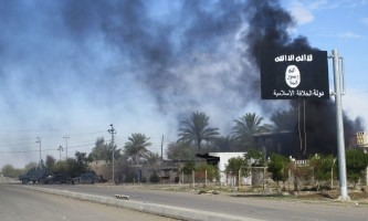 Smoke raises behind an Islamic State flag after Iraqi security forces and Shiite fighters took control of Saadiya in Diyala province from Islamist State militants, November 24, 2014. Iraqi forces said on Sunday they retook two towns north of Baghdad from Islamic State fighters, driving them from strongholds they had held for months and clearing a main road from the capital to Iran. There was no independent confirmation that the army, Shi'ite militia and Kurdish peshmerga forces had completely retaken Jalawla and Saadiya, about 115 km (70 miles) northeast of Baghdad. Many residents fled the violence long ago. At least 23 peshmerga and militia fighters were killed and dozens were wounded in Sunday's fighting, medical and army sources said.  REUTERS/Stringer (IRAQ - Tags: CIVIL UNREST CONFLICT MILITARY TPX IMAGES OF THE DAY)
