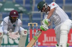 Pakistani batsman Younis Khan (R) plays a shot as West Indies' wicketkeeper Shai Hope looks on during the first day of the second Test between Pakistan and the West Indies at the Sheikh Zayed Cricket Stadium in Abu Dhabi on October 21, 2016.  Pakistan won the toss and decided to bat in the second Test against West Indies played at Sheikh Zayed Stadium. / AFP PHOTO / AAMIR QURESHI